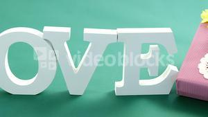 Gift box and alphabet love on green background