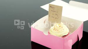 Cupcake with happy mother day card against black background