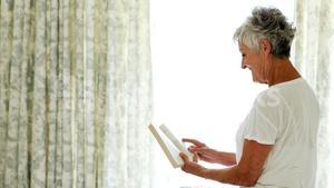 Smiling senior woman reading book in bedroom