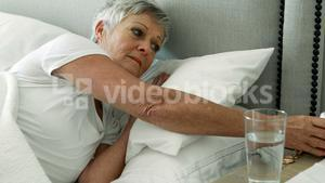 Senior woman turning off alarm clock in bedroom