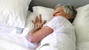 Senior woman sleeping on bed in bedroom