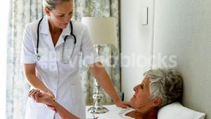 Female doctor checking senior woman pulse during check up in bedroom