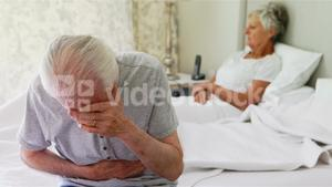 Upset senior couple arguing with each other in bedroom