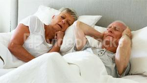 Senior man covering his ears while woman snoring in bedroom