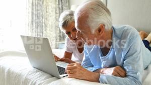 Smiling senior couple using laptop on bed in bedroom