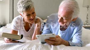 Senior man using digital tablet while woman reading a book on bed