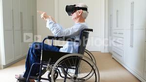 Senior man on wheelchair using vr headset in bedroom
