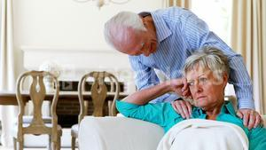Upset senior couple arguing with each other in living room