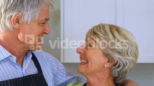 Smiling senior couple interacting with each other in kitchen
