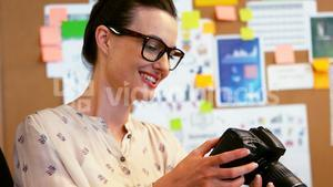 Graphic designer looking at digital camera in creative office