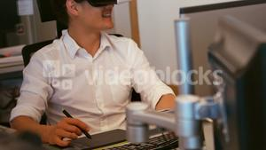 Graphic designer using virtual reality headset while working in office