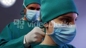 Surgeon helping a nurse in tying surgical mask in operation room
