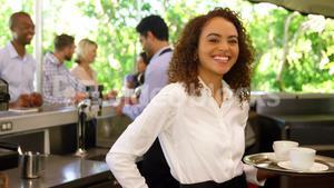 Female waitress serving coffee to customers
