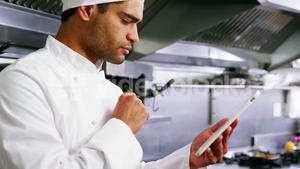 Male chef using digital tablet in commercial kitchen