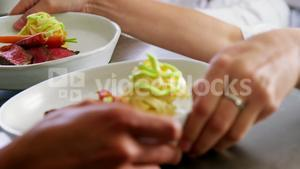 Team of chefs holding food dishes in commercial kitchen