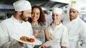 Team of chefs holding food plate in commercial kitchen