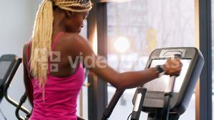 Fit woman exercising on cross trainer