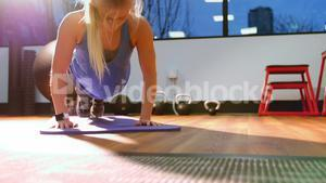 Fit woman performing push-up on exercise mat