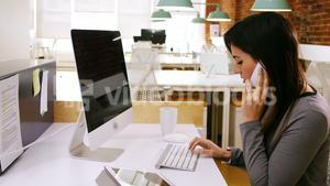 Female executive talking on mobile phone while working on computer at desk