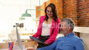 Male and female executives discussing over digital tablet at desk
