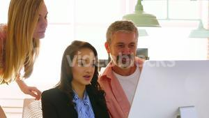Male and female executives discussing over computer