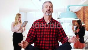 Male executive performing yoga while his executive standing in background