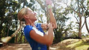 Fit woman climbing rope during obstacle course