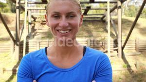 Smiling fit woman standing with arms crossed in park