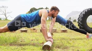Fit man and woman doing pushup during obstacle course