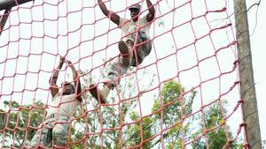 Military soldier climbing rope during obstacle course