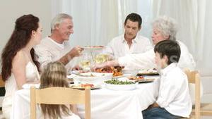 Panorama of parents, children and grandparents having dinner at home