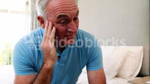 Tense senior man sitting on bed in bedroom