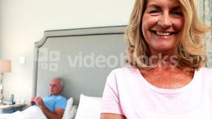 Portrait of smiling woman while men lying on bed