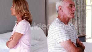 Upset senior couple sitting back to back on bed