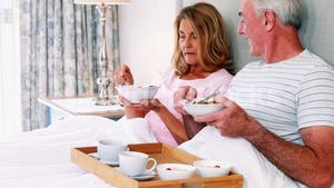Smiling senior couple having breakfast on bed