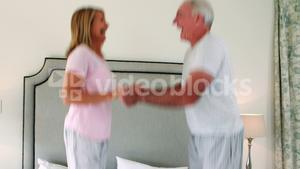 Happy senior couple dancing on bed