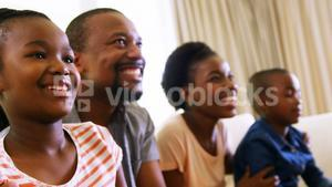 Parents and kids playing video games in living room