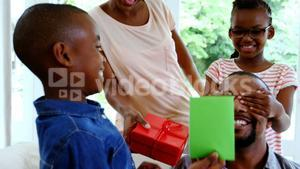 Loving kids and mother are giving present to their father in living room