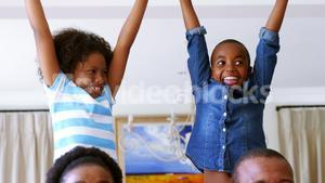 Kids and parents cheering while watching match on television in living room