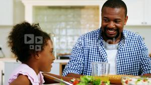 Father and daughter having meal on dinning table at home
