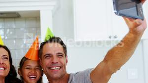 Happy family taking a selfie while celebrating a birthday