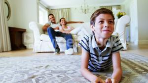 Parents and son watching television in living room