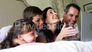 Happy family using laptop on bed in bedroom