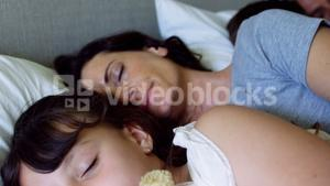 Parents and kids sleeping together on bed in bedroom