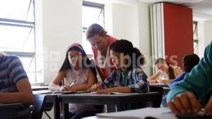 Teacher helping students with their homework in classroom
