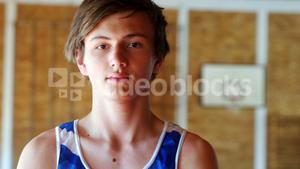 Portrait of schoolboy standing in basketball court