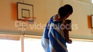 Two schoolboys playing basketball in basketball court