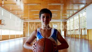 Portrait of schoolboy holding basketball in basketball court