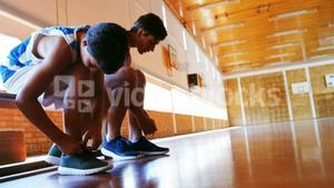 Two schoolboys tying shoe laces in basketball court