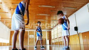 Schoolboys playing basketball in basketball court